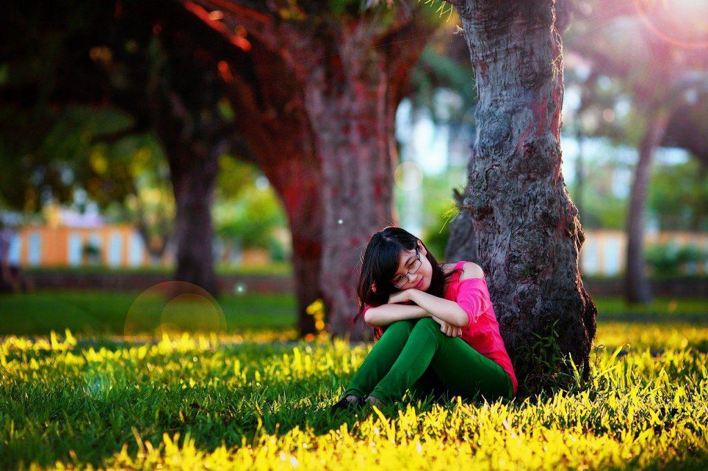 公園の木の下で考え事をする女の子の写真