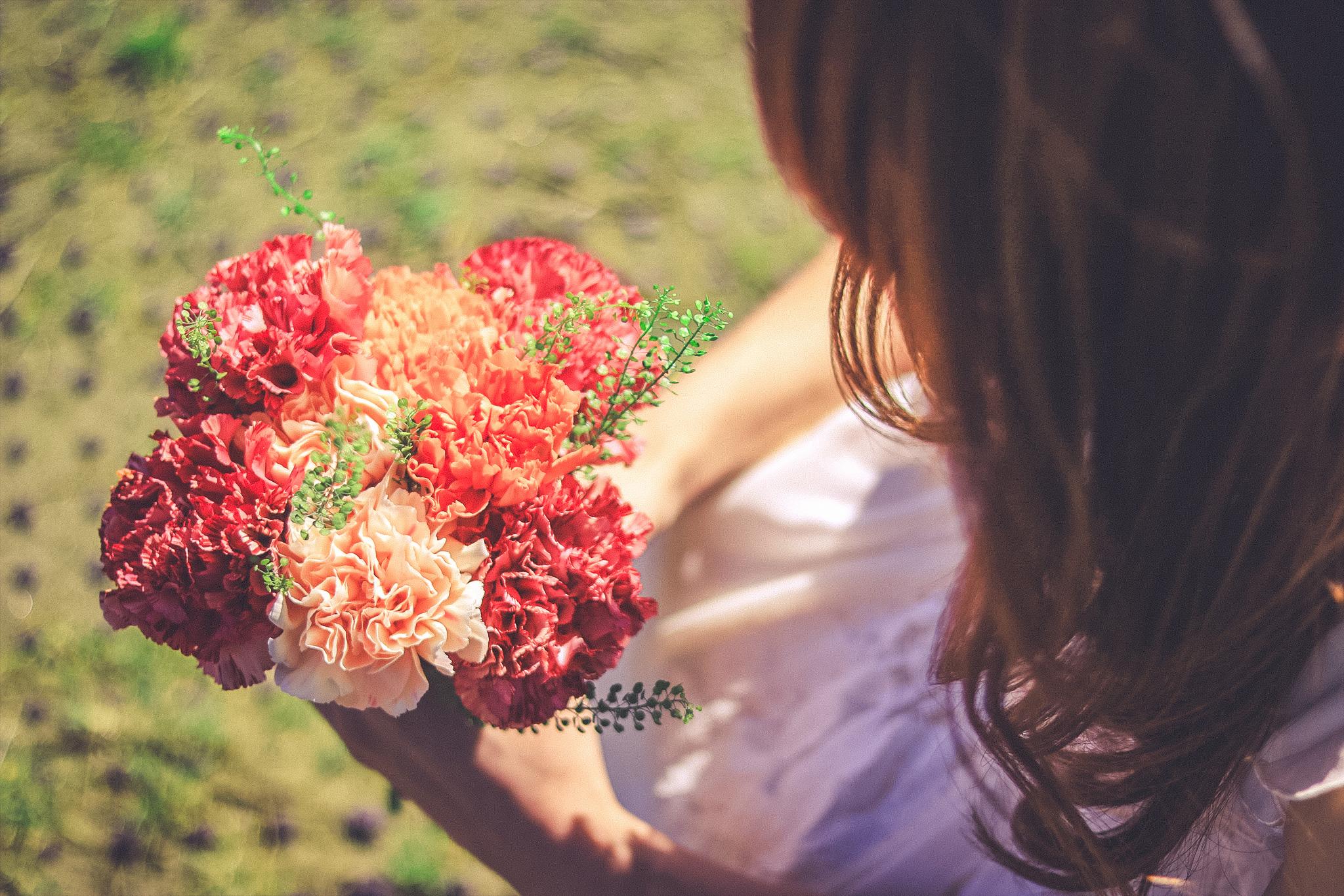 花束を見つめる女の子の写真